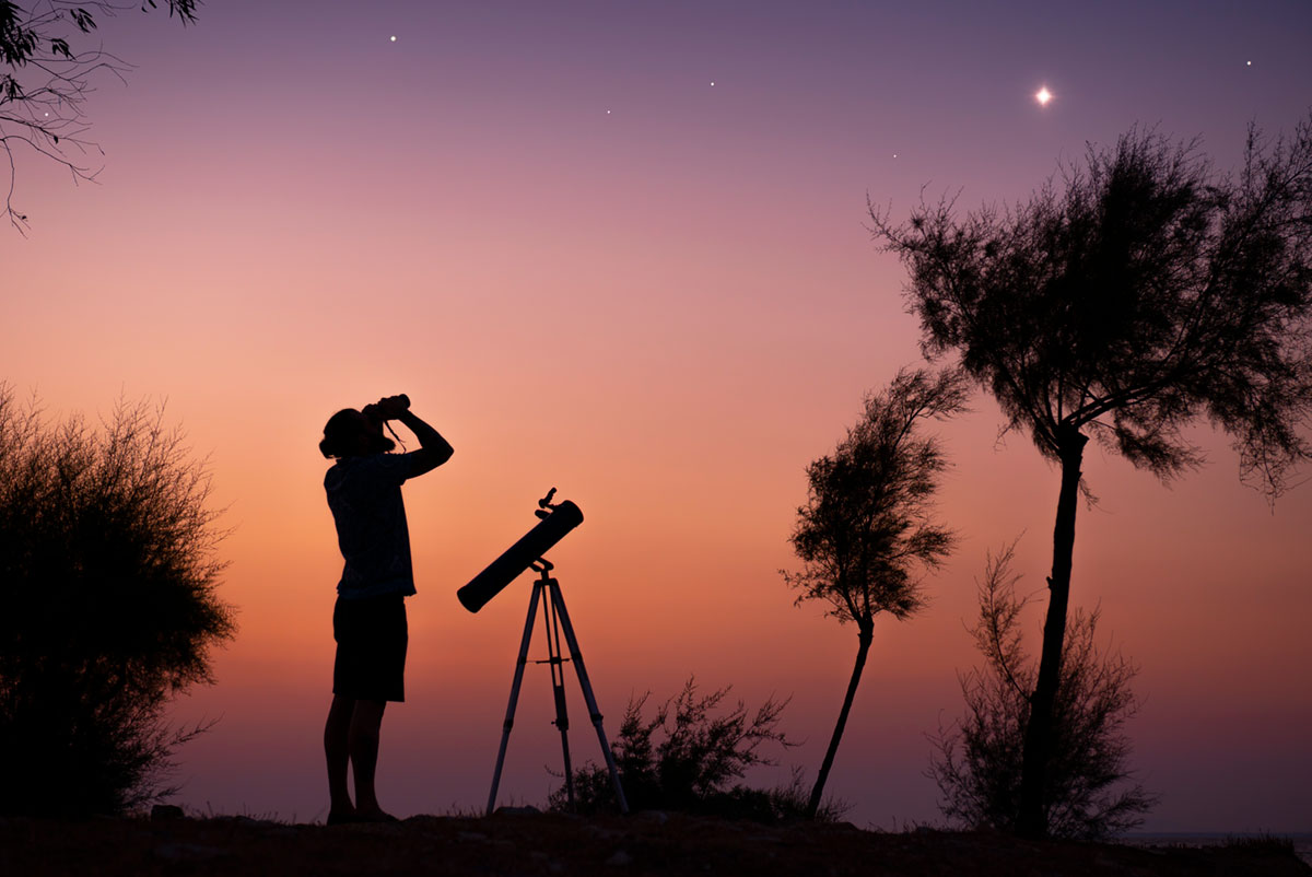 A man standing next to a portable telescope uses binoculars to observe stars in the twilight sky