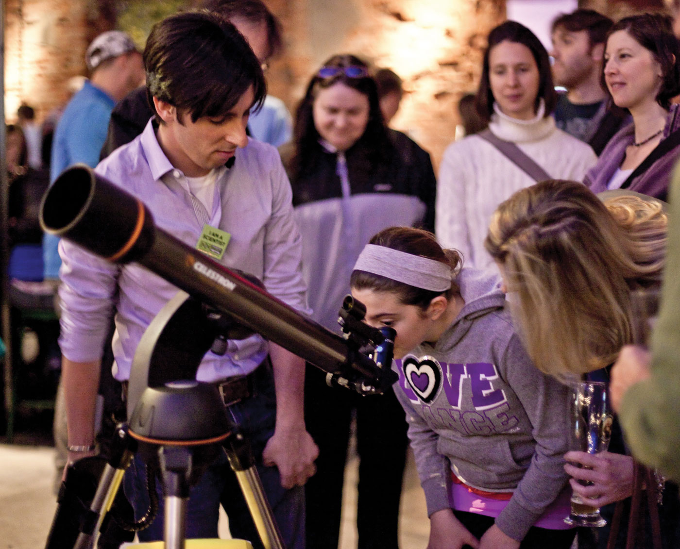A girl looking through a telescope during a City Skies event.