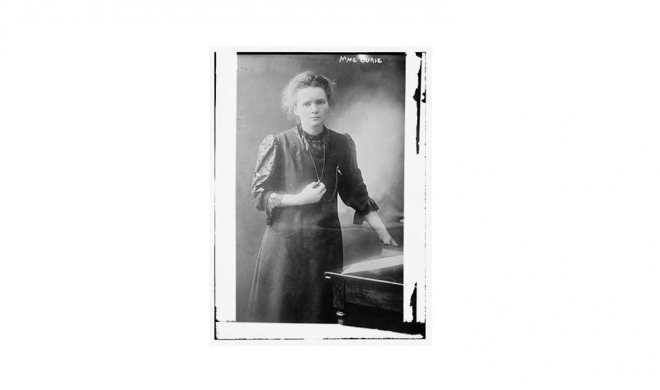 Black and white historical image of Marie Curie standing