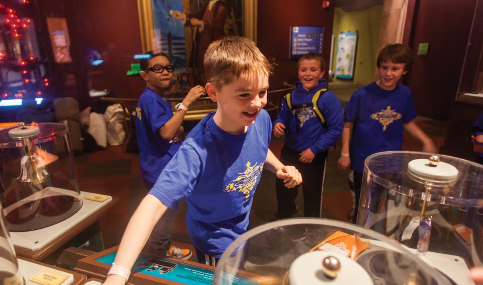 A group of boy scouts having fun in the Electricity exhibit at The Franklin Institute.