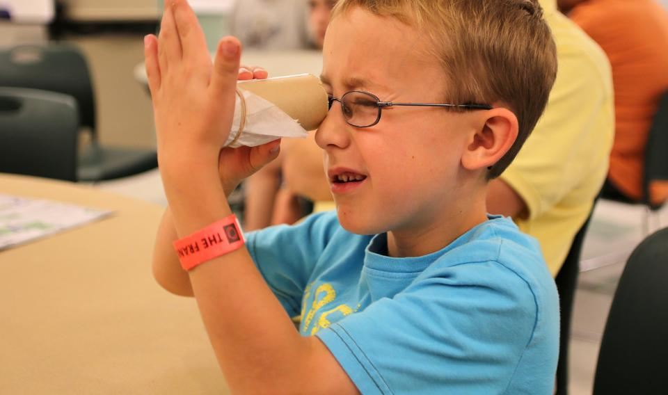 Boy looking through a paper towel tube learning and exploring during a Member Sunday workshop.