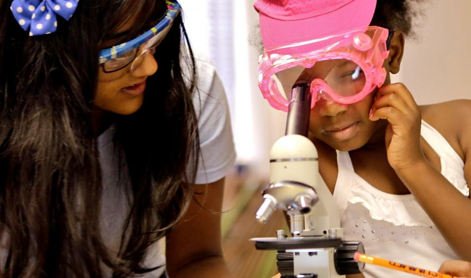 Girls at a workshop looking through a microscope at The Franklin Institute.