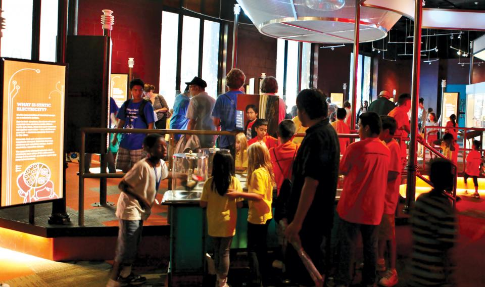 Multiple groups of visitors wandering the Electricity exhibit at The Franklin Institute.