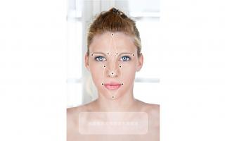 A picture of a woman's face overlaid with a facial recognition pattern.