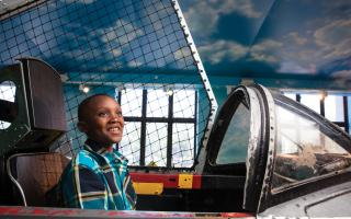 A boy sitting inside the T-33 Jet Trainer in the Franklin Airshow exhibit at The Franklin Institute.