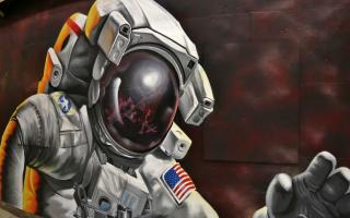 """""""Reflections of Greatness"""" mural of an Astronaut in space, with ISS reflected and Earth in the background."""