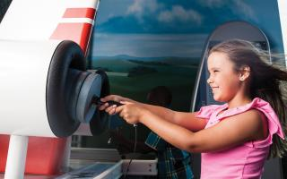 A young girl is playing with and learning from an interactive about wind, in the Franklin Insitute's permanent exhibit, Franklin Air Show.