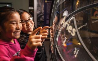 Two younger girls looking at the constellation globe in Space Command.