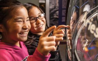 Two younger girls looking at the constellation globe in Space Command at The Franklin Institute.